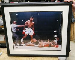 "Picture of "" MUHAMMAD ALI KNOCKS OUT SUNNY LISTON"" . AUTOGRAPHED. FRAME SIZE 22X25 . PICTURE SIZE 19X22. WITH GRANDSTAND SPORT HOLOGRAM, ONLINE AUTHENTIC HOLOGRAM ."